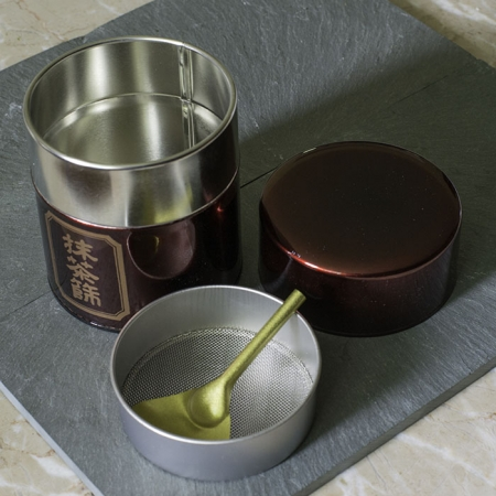 Buy Online - Matcha strainer tin. This airtight storage tin has an integrated mesh strainer and strainer spoon to remove clumps from matcha. All in a beautiful presentation.
